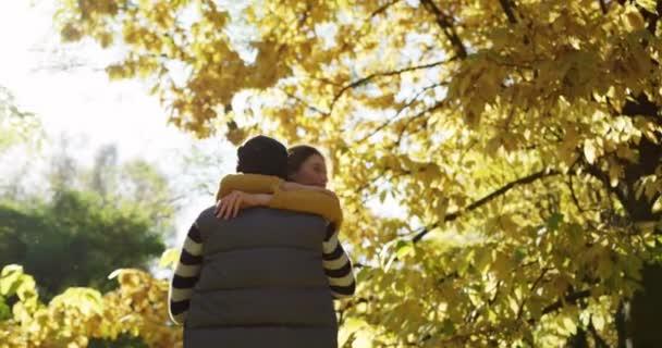 Mladý šťastný pár spinning pod žluté stromy v malebném parku. Slunečné počasí na podzim. Venku