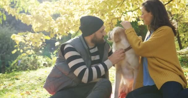 Portrait of young attractive man and woman sitting in the autumn park and playing with their dog in the fall. Labrador licking the mans nose. Outside
