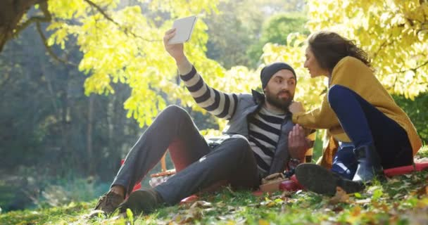 Young happy couple making lovely selfies on the tablet computer in the autumn park among yellow trees. Sunny day. Outdoors