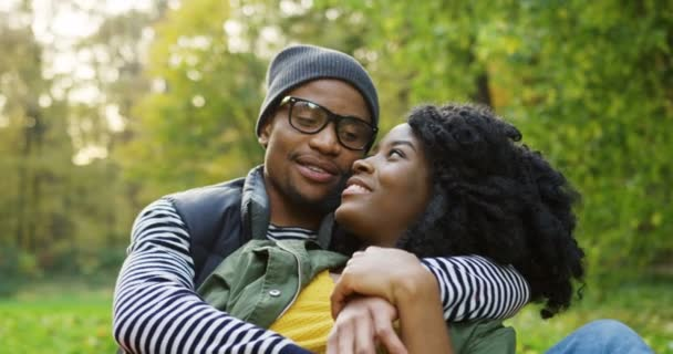 Close up of young lovely African American couple hugging and dreaming in the autumn park. The sunny weather. Outdoors. Portrait