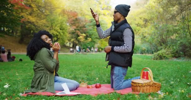 African American couple having a picnic in the park. Young man taking photos of curly woman with an apple. Autumn sunny day. Outside