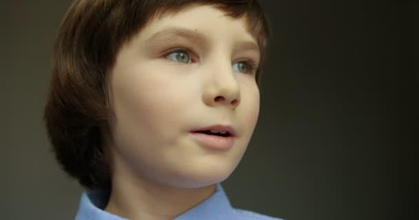 Detail portrét roztomilého chlapečka v modré košili dívá do kamery a usmívá.