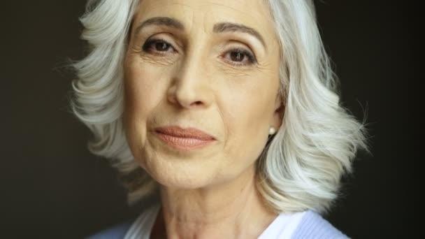 Zavřete portrét šťastné staré ženy soustružení a usmívá se na kameru. Vnitřní záběr.