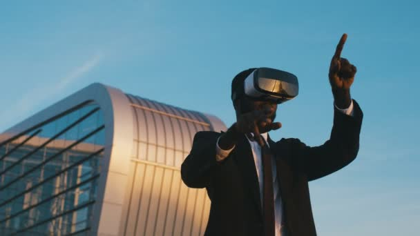 Portrait of African American young businessman in suit and tie having VR headset on the big urban glass building background. Man in VR glasses scrolling in the air on the blue sky background. Outdoors