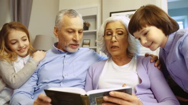 Prarodiče s vnoučaty, čtení knihy dohromady sedíte na pohovce v obývacím pokoji.