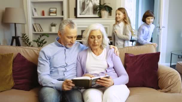 Nahaufnahme von Großeltern, die Buch lesen, während ihre Enkel ins Zimmer kommen und zu Hause auf dem Sofa sitzen.