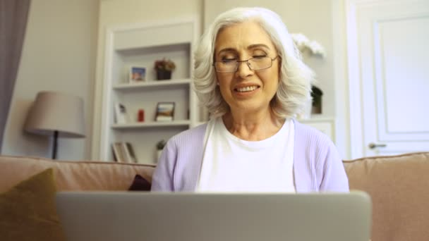 3ad4986406 Close up shot of happy old woman in glasses using laptop for video chatting  at home in the living room.– stock footage