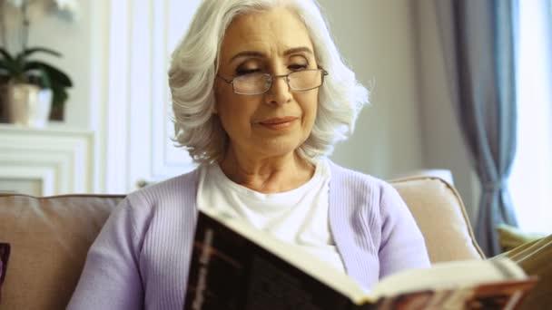 Zblízka portrét ženy s brýlemi odpočinku na gauči doma a čtení zajímavé knihy.