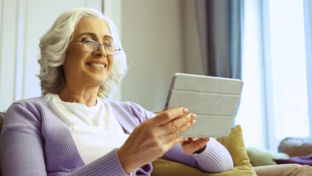 Nahaufnahme einer schönen alten Frau mit Brille, die mit einem Tablet zu Hause im Wohnzimmer im Internet surft.