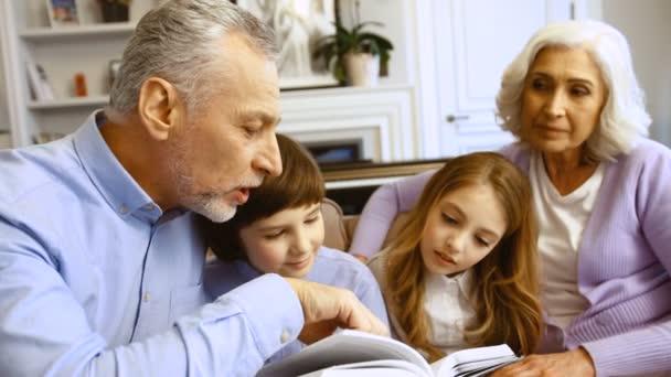Portrét roztomilý prarodičů s jejich vnoučata čtení zajímavý příběh z knihy dohromady při sezení na pohovce v obývacím pokoji. Detailní záběr