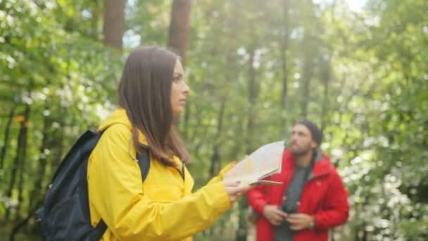 Mladá žena a muž s batohy Hledat trasu pomocí mapy a dalekohled. Zabloudit. Venku