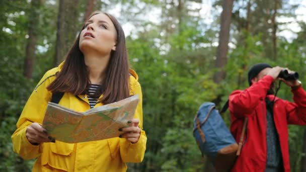 Young couple with backpacks getting lost in the forest and looking for the way back with a help of map and binoculars. Outside