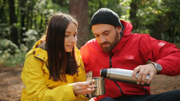 Portrait of handsome man pouring hot tea to the charming young woman from a thermos while they sitting and smiling in the forest. Outdoors