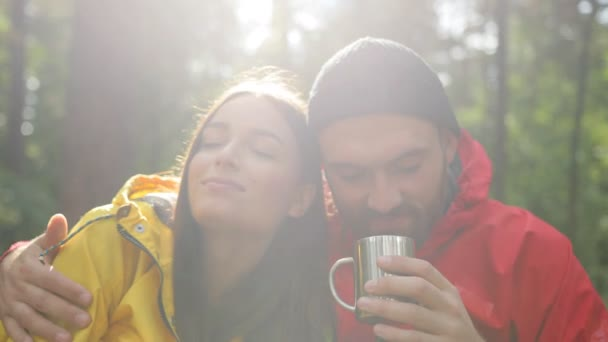 Close up of young couple drinking hot tea from a thermos while they having rest in the amazing forest in a sunlight. Outdoors. portrait