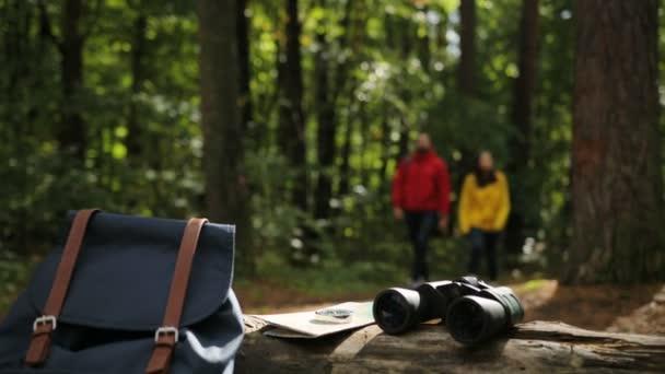Detailní záběr, batoh, mapu a dalekohledy na kufru v lese. Rozmazané pozadí sportovní mladé ženy a muže, pěší turistika. Vně