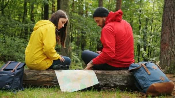 Mladý sportovní turisty žena a muž s batohy, mapu, dalekohled a kompas plánování jejich trasy v lese, zatímco sedí na kufru. Zabloudit. Vně