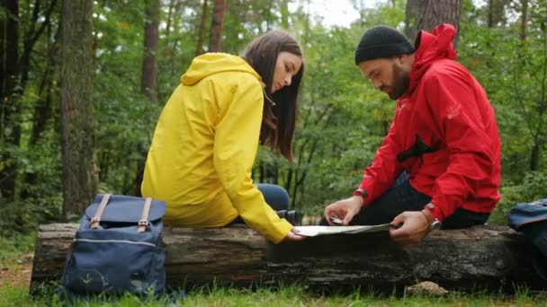 Mladá atraktivní žena a muž s batohy, mapu a dalekohledem hledal správnou cestu s pomocí kompasu v lese zatímco sedí na shuft. Zabloudit. Pohled zezadu. Venku
