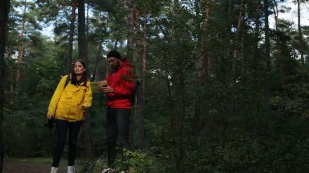 Mladá sportovní žena a muž s batohy Hledat trasu pomocí mapy a usmíval se v zeleném lese. Zabloudit. Vně