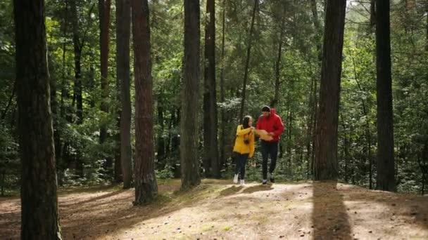 Fiatal turisták pár színes kabátok és hátizsákok, séta az erdőben, és keresi a térképen. A szabadban
