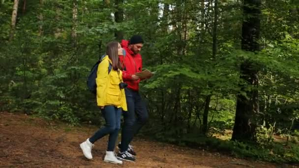 Young lovely couple with backpacks walking in the middle of the beautiful green forest and looking at the map. Outdoors