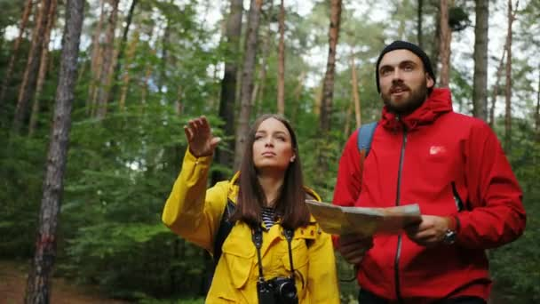 Portrait shot of the sporty couple in colourful coats and with backpacks strolling in the forest and looking for a way back with a map in hands. Got lost in the forest. Outdoor