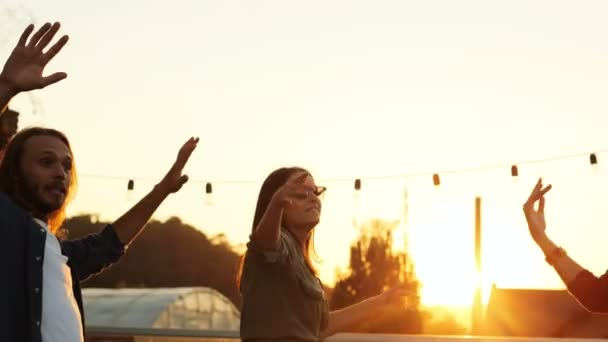 Silhouettes of young parting people dancing in circle and giving fives at the rooftop party in urban space. The sunset background. Outside. Multiethnic