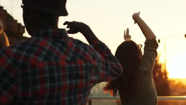 Parting friends dancing and giving fives at the rooftop party in urban space. The sunset background. Outdoor. Multiethnic