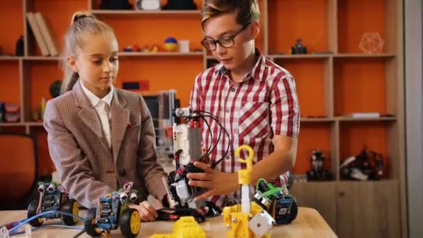 Portrait shot of girl and boy in glasses talking and mastering a robotic machine in the orange playing classroom