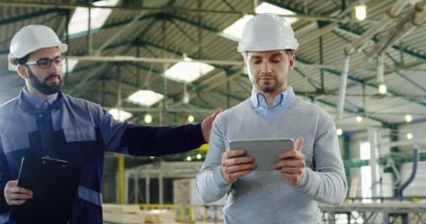Handsome engineer in a helmet taping and scrolling on his tablet when factory worker in a helmet coming to him, men shaking hands and discussing what they seeing on a tablet screen in the factory