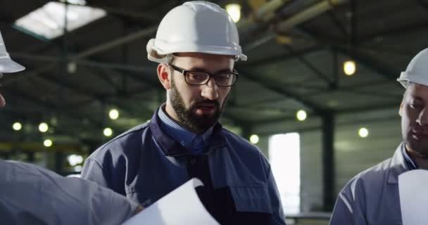 Nahaufnahme von drei Ingenieuren in Helmen mit großen Papierzeichnungen, die sich unterhalten und über ihr Arbeitsprojekt diskutieren. Planung in einem großen Werthaus. Porträtaufnahme