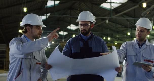 Tři inženýři v přilbách s velkými papírové výkresy chůzi a diskusi o jejich projektu. Plánování uvnitř velké manufaktury.