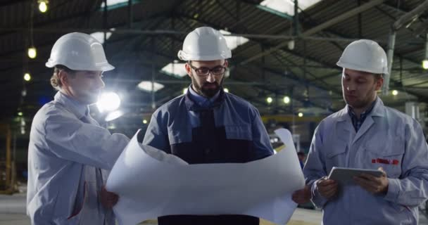 Portrait of three engineers in helmets with a tablet and big paper drawings having a talk and discussing their work project. Inside a big factory.