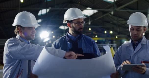 Portrét shot tří inženýrů v přilbách s tablet a velkých papírových výkresů diskutovat o jejich nový projekt práce. Uvnitř velké manufaktury