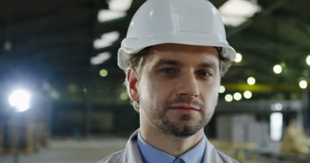 Close up of the attractive Caucasian engineer in a helmet turning his head to the camera and smiling. The big manufactory werehouse on the blurred background. Portrait shot