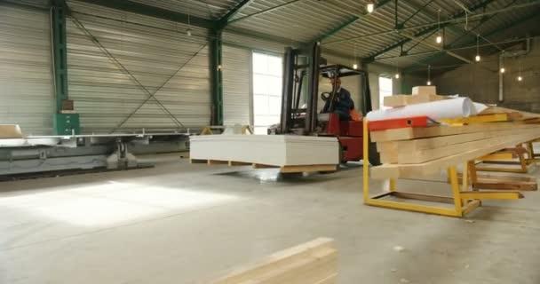 Pracovní den v továrně na dřevo. Elektro auto přepravující řezání dřeva prostřednictvím velkých průmyslových zařízení. Vnitřní
