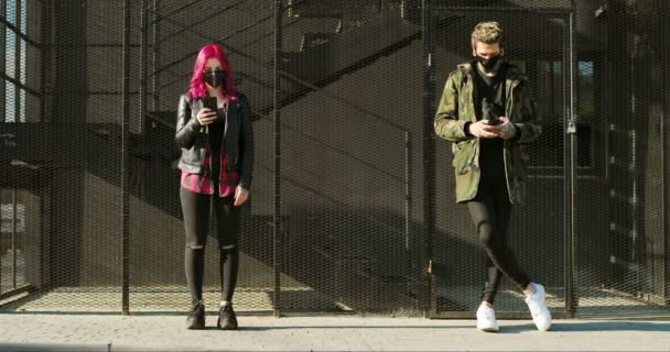 Caucasian couple of extraordinary hipsters in masks keeping social distance outdoors. Girl with pink hair tapping and typing on mobile phone and guy texting or scrolling on smartphone. Playing online.