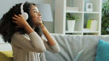 Beautiful curly African American young woman in the white headphones listening to the music, moving in rhythm and working on her laptop at home.