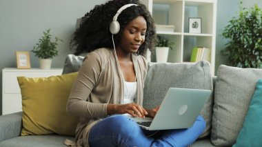 Young curly African American woman in the white headphones taping on her laptop while sitting on the couch in the living room.