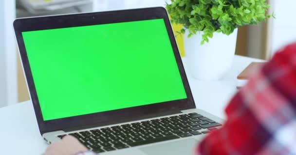 Tekintse át a vállát laptop számítógépen van az asztalon zöld képernyővel. Krómkulcs. Fehér nő kopogtat és gépel a billentyűzeten. Női szabadúszó dolgozik otthon online.