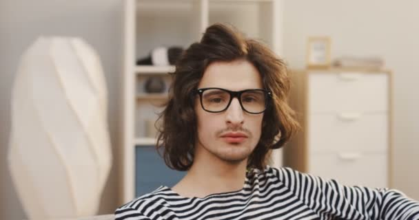 Close up of the young Caucasian man with a long hair and in glasses looking at the side then turning his head to the camera in the light living room. Portrait. Indoor