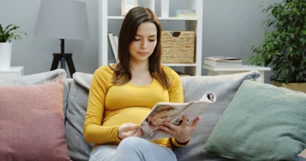 Pěkně těhotná žena sedí na gauči s polštáři a čte si časopis v útulném obýváku. Vnitřní