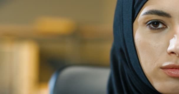Close up of half female face of beautiful young muslim woman in black hijab indoor. Portrait of Arabian charming lady with dark eyes smiling to camera in office. Businesswoman in traditional headscarf
