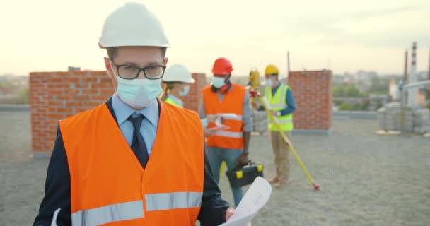 Porträt eines kaukasischen Jungunternehmers, der in Hemet und medizinischer Maske am Gebäude steht und den Entwurf des Bauplans in den Händen hält. Männlicher Ingenieur oder Architekt am Bau bei Pandemie.