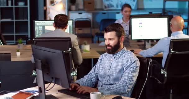 Happy Caucasian bearded man sitting at the desk and rejoices in successful outcome. Concept of work in coworking.