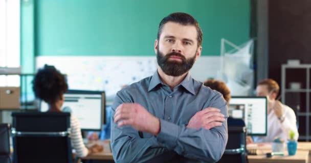 Portrét pohledného bělocha s vousy v šedé košili zkříží ruce na prsou a usmívá se na kameru, když stojí v úřadu.