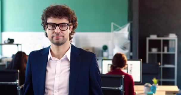 Portrét úspěšného obchodníka v obleku stojící uprostřed kanceláře. Hezký muž s brýlemi, dívá se do kamery a zkříží ruce na prsou.