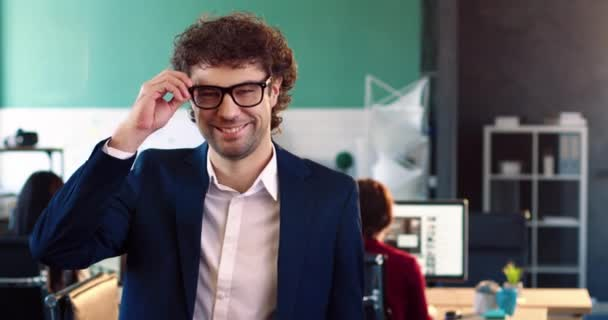 Portrét úspěšného obchodníka v obleku stojící uprostřed kanceláře. Hezký muž si sundá brýle a usměje se na kameru.