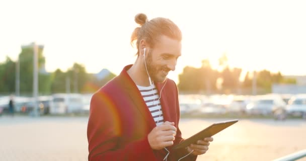 Caucasian young handsome man in headphones and red jacket tapping, scrolling and listening to music on tablet device. Cheerful happy male using gadget at car parking. Cars on background.