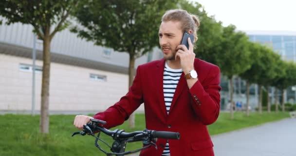 Kavkazský mladý pohledný muž v červené bundě stojí na ulici na kole nebo elektrický skútr a mluví na mobilním telefonu. Stylový chlap venku mluví na mobilu. Kolo. Cyklista mluvit po telefonu.