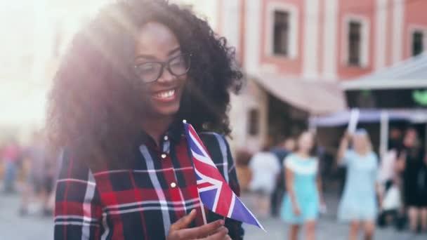 Gyönyörű afro-amerikai lány kockás ingben az utcán áll és Nagy-Britannia zászlaját tartja. Közelkép portré fiatal cserediák buja göndör haj.